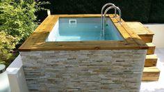 Mini piscine en bois avec habillage en pierre de parement.