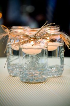 Mason jar centerpieces with floating candles. [UPDATED These DIY Mason Jar Centerpieces can also be made into favors. Use the lanterns to provide light to your wedding tables. Floating Candle Centerpieces, Rustic Wedding Centerpieces, Simple Centerpieces, Easy Table Decorations, Wedding Favors, Wedding Tables, Party Favors, Wedding Ceremony, Party Centerpieces