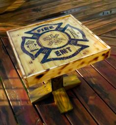 Little deck table I made for a firefighter/EMT related fundraiser. Made from scrap wood I had left over... design is imprinted with a woodburner and scorch marks around the edge were done with a torch.