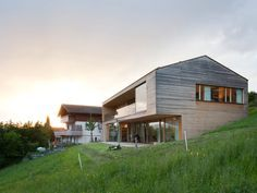 the dwelling by dietrich untertrifaller is nestled into the steep hill with terraces on both floors looking out to the pristine landscape.