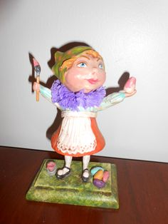 "GIRL PAINTING EASTER EGGS, 8"" tall, head turns Original Debra Schoch piece.  2013. Paper Clay Material."