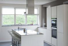 Strak witte keuken met kookeiland.