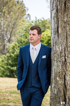 San Diego outdoor beach wedding groom dark navy blue suit with matching vest and white dress shirt with a long ivory tie and matching pocket square