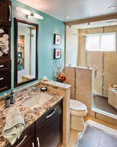 The dark brown vanity in this contemporary bathroom provides a striking contrast to a vibrant turquoise accent wall. A convenient shelving unit sits to the left of a coordinating mirror, providing ample space for easy-to-reach bathroom necessities.