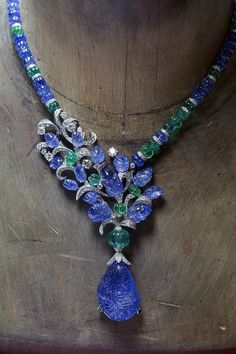 L'Odyssée de Cartier high jewellery - A.lain R. T.ruong  ||  Necklace in platinum, set with a 67.94ct carved sapphire, melon-cut sapphire, emerald beads, sapphire carved leaves and diamonds.   Photo by courtesy of Cartier.