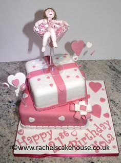 21st birthday cake, a lady in a martini glass bath full of bubbles, with white and pink hearts and icing ribbon, off set tiers finish off this bespoke two layer celebration birthday cake.