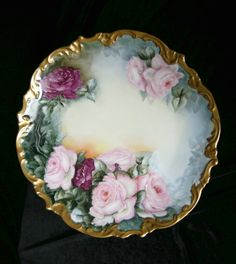 antique W.G. and Co. Limoges porcelain charger with beautiful pink and burgundy cabbage roses. The roses are exquisitely hand painted by the artist!   There is beautiful raised relief detail along the scalloped edges. These edges are heavily gilded. The gildis 99% intact.   It is marked with the William Guerin Limoges France mark which dates it 1891 to 1932.