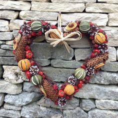 decoracion navideña manualidades, pared de piedra, corona navideña con forma corazon, piñas, limas y naranjas