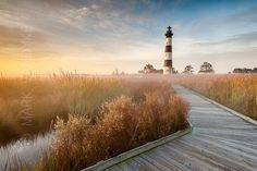 The sun rises behind the historic Bodie Island Lighthouse on North Carolina's Outer Banks as radiant fog sits low to autumn marsh grasses.