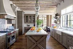 In Gisele Bündchen and Tom Brady's Los Angeles home, antique Tunisian tile from Exquisite Surfaces makes a lively backsplash in the kitchen, which is appointed with Formations pendant lights, marble countertops from Compas Architectural Stone, custom-made alder cabinetry, an oak island, and a Wolf range.