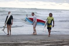 Three surfers in guiones beach Nosara, Costa Rica