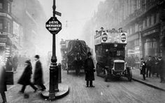 A policeman stops the traffic and helps pedestrians cross the road at Ludgate Circus (1914).