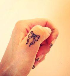Piccolo fiocco tatuato sul dito