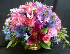 A low bowl arrangement consisting of roses, orchids and hydrangea in a pink color scheme with accents of blue thistle. See our entire selection at www.starflor.com.  To purchase any of our floral selections, as gifts or décor, please call us at 800.520.8999 or visit our e-commerce portal at www.Starbrightnyc.com. This composition of flowers is generally available for same day delivery in New York City (NYC).  C165