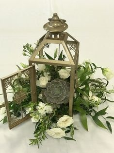 Gold lantern filled with succulent, white blooms of stock, lisianthus, spray roses and mixed greens of Italian Ruscus, olive leaf and rosemary. Lantern Centerpiece Wedding, Wedding Reception Table Decorations, Succulent Centerpieces, Wedding Lanterns, Wedding Centerpieces, Wedding Ideas, Lanterns With Flowers, Large Lanterns, White Lanterns