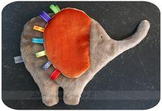 Doudou étiquette éléphant réalisé sur commande.  Doudou étiquettes en forme de éléphant. Matière douce en douillette dont les coloris sont à choisir parmi les coloris  - 19204025