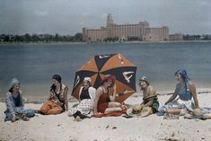 Florida - Six women sit on a St. Petersburg beach with the water behind them.  1920-30's