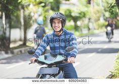 portrait of happy asian man riding on motorbike in city street