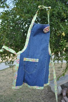 This apron is made from the leg of a pair of jeans with adorable fabric accents. The fabric has a lime or light green background with various