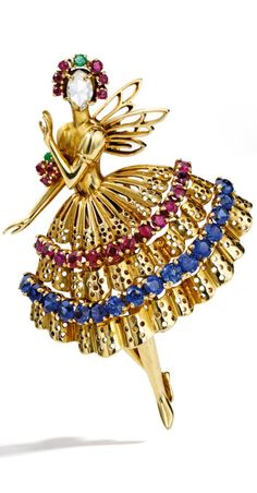 18 Karat Gold, Ruby, Sapphire, Emerald and Diamond 'Ballerina' Brooch, Van Cleef & Arpels, New York. The winged ballerina decorated with a tiara and floral bouquet, her costume designed with an openwork full skirt, the face set with a rose-cut diamond, further highlighted with round sapphires, rubies and emeralds, gross weight approximately 12 dwts, signed Van Cleef & Arpels N.Y., numbered 12948; circa 1947.