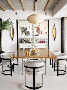 Sala de jantar com mesa de madeira e cadeiras estofadas