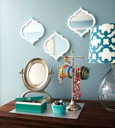 Well-done storage in a master bedroom offers a charming combination of decorative accents and practical storage. Here, a pretty trio of mirrors adds visual interest to a wall, while a place mat gathers together jewelry holders.