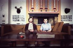 Film Editor Ray Lovejoy, left, sits next to Stanley Kubrick's longtime personal assistant Emilio D'Alessandro on the The Shining's Colorado Lounge set.  Lovejoy, who had previously edited for Kubrick on 2001: A Space Odyssey, was unable to complete his editing duties on The Shining due to a hand injury. Second Assistant Editor Gordon Stainforth stepped in and finished editing the film with Kubrick.  On the table in front of them sits the Overlook Hotel scrapbook, a prop which, although it…