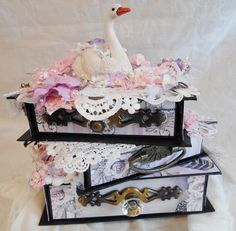 "This is an altered book stack using Dreamz...Etc... digital paper kit ""Black Swan"" This shabby chic altered paper mache book stack has been embellished with laces, appliques, flowers, feathers, charms and much more. The 2 upper drawers pull out for storage of keepsakes and trinkets and the lower drawer pulls out into a 5 1/2 x 7 1/2 mini album/journal. I can be reached at APawSpa@aol.com for the sale of this piece or a custom creation.  https://www.youtube.com/watch?v=hj6mCeHzxh0"