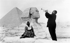A 1961 New York Times photo, showing Louis Armstrong playing trumpet for his wife, Lucille, in front of the Great Sphinx and pyramids in Giza, Egypt.