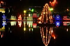 Christmas lights are reflected in the lake at City Park Friday evening.