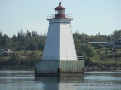 Sandy Point Lighthouse - This attractive lighthouse, which originally was built on a pier, now sits on a crib at the east side of the entrance to Shelburne Harbour.  At low tide the tapered wooden tower is accessible across a sand bar.  There is a sandy beach, swimming, birding and a community hall where snacks may be available.  Many festivals and activities take place here in the summer, especially lobster dinners. Lighthouse Trails, East Side, Nova Scotia, Lighthouses, Crib, Festivals, Entrance, Dinners, To Go