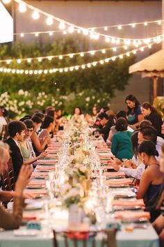 Guests enjoy the outdoor wedding reception under romantic strings of lights.
