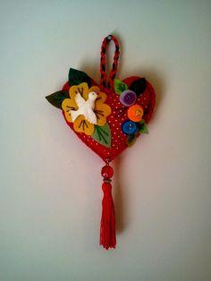 Pingente coração em feltro, decorado com Divino em biscuit, flores, miçangas, contas, cordão de cetim e franja. <br>Ideal para decorar trincos e maçaneta de porta, para enfeitar algum cantinho especial e trazer proteção e alegrar sua casa.