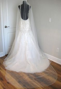 Single tier, cathedral veil measuring roughly 113 in length. The veil comes with a metal comb and its covered in three different sizes of crystals. The tulle used to make these veil are high quality and very soft. Please note that the length of the veil is a rough estimate. Each veil may slightly differ because they are all handmade. Let me know if you are interested or have any questions.