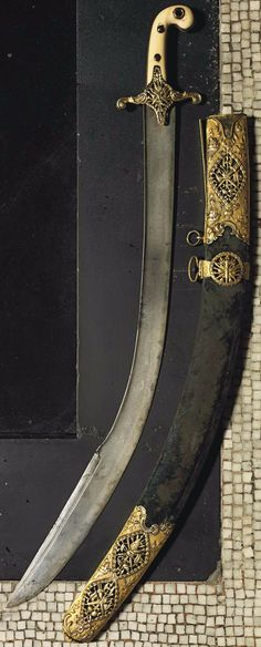 "Ottoman kilij, (smaller version known as ""pala"") late 18th century, watered steel blade, blunt edge decorated with confronted cast palmettes, gilded crossguard with stylised openwork depiction of the Ottoman Imperial coat-of-arms, ivory grip with gilt studs, velvet covered scabbard with gilt openwork coat-of-arms on a ground decorated in repoussé with military and architectural scenes, cannons on a punched ground, rococo foliage borders above and below, 34in. (86.4cm.) long."