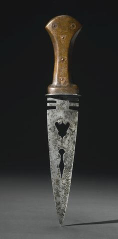 Rare Northern Plains Wood and Steel Dag Knife, with a paddle-style wood handle, decorated with triangular and circular metal inlay, the notched forged steel blade, probably from a war lance, pierced with a batwing design surmounted by a stylized dag knife effigy. length 14 1/4 in. Acquired from Fred Crissman, Pittsburgh PA.  Sotheby's. ARTS OF THE AMERICAN WEST 21 MAY 2014. NEW YORK.