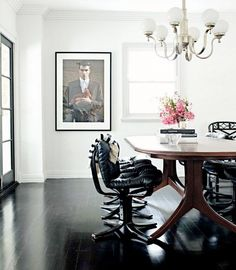 // pristine white dining room, graceful chandelier, given some edge with black leather chairs