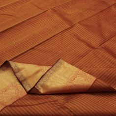 Gabled vertical stripes in golden mustard and maroon create delicious ripples in #silk across the body of this timeless #Kanjivaram. Floral and peacock silhouettes in gold embellish the shimmering and wide border on either side. The russet terracotta pallu comes alive with the glimmer of gold stripes and peacocks woven in zari. For saris in this exotic colour, visit Sarangi. Code 120124641.