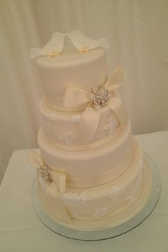 Wedding cake , brooches, ivory ribbon, lace, love birds.