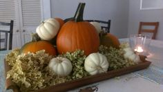 Fall Centerpiece of pumpkins, candles, dried hydrangeas from home, and a wooden serving tray.