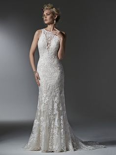 22192 - Winifred - Timeless and elegant, this lace sheath wedding dress features a modern illusion deep V halter neckline, a stunning, scalloped plunging back, and illusion straps  Try this beauty on at Aurora Bridal in Melbourne, FL 321-254-3880
