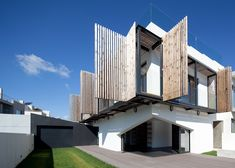 Slatted timber shutters fold back to reveal the boxy first-floor balcony of this family house in Portugal.