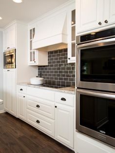 The new vent hood is wrapped in wood and painted white to match the cabinetry.The backsplash is charcoal gray glass tile.