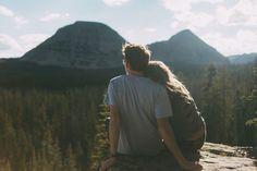 Pareja de novios sentados en una roca en las montañas viendo el horizonte
