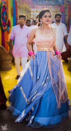 Stunning peach and blue ruffled lehenga with a belted dupatta for a holi themed function Indian Suits, Indian Attire, Indian Dresses, Indian Wear, Punjabi Suits, Indian Style, Indian Ethnic, Bollywood Lehenga, Lehenga Choli