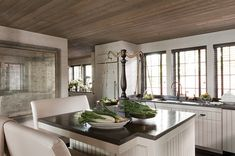 """The kitchen can be both functional and decorated """"A foxed mirror with a distressed gilt frame brings the same reflectivity and finery found elsewhere in the house into the otherwise simple kitchen."""""""
