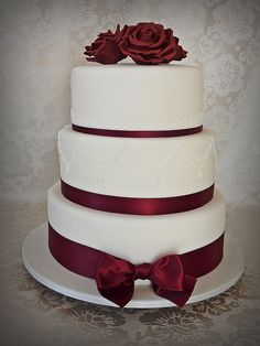 White cake with simple, chic designs & deep red ribbon & roses. Can be done in buttercream as well!