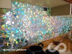 Отделка рабочей стены на кухне мозаикой из компакт-дисков.