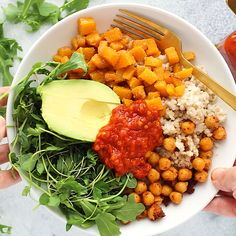 These Butternut Squash Buddha Bowls are the most colorful meal you'll ever eat! They're made with brown rice, crunchy chickpeas, roasted butternut squash, greens, avocado, and harissa sauce. Make a double batch of these bowls for a healthy and delicious meal prep recipe for the week!