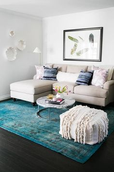 Learn how to make a small living room look bigger [with mirrors, lucite furniture, neutral colors] and by adjusting your furniture layout.